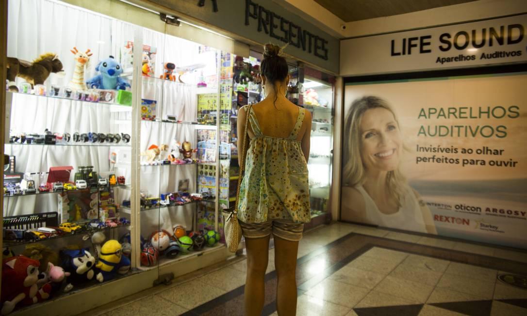 Consumidora diante de vitrine em Niterói: consumidor longe das lojas Foto: Maria Isabel Oliveira/4-2-2021 / Agência O Globo
