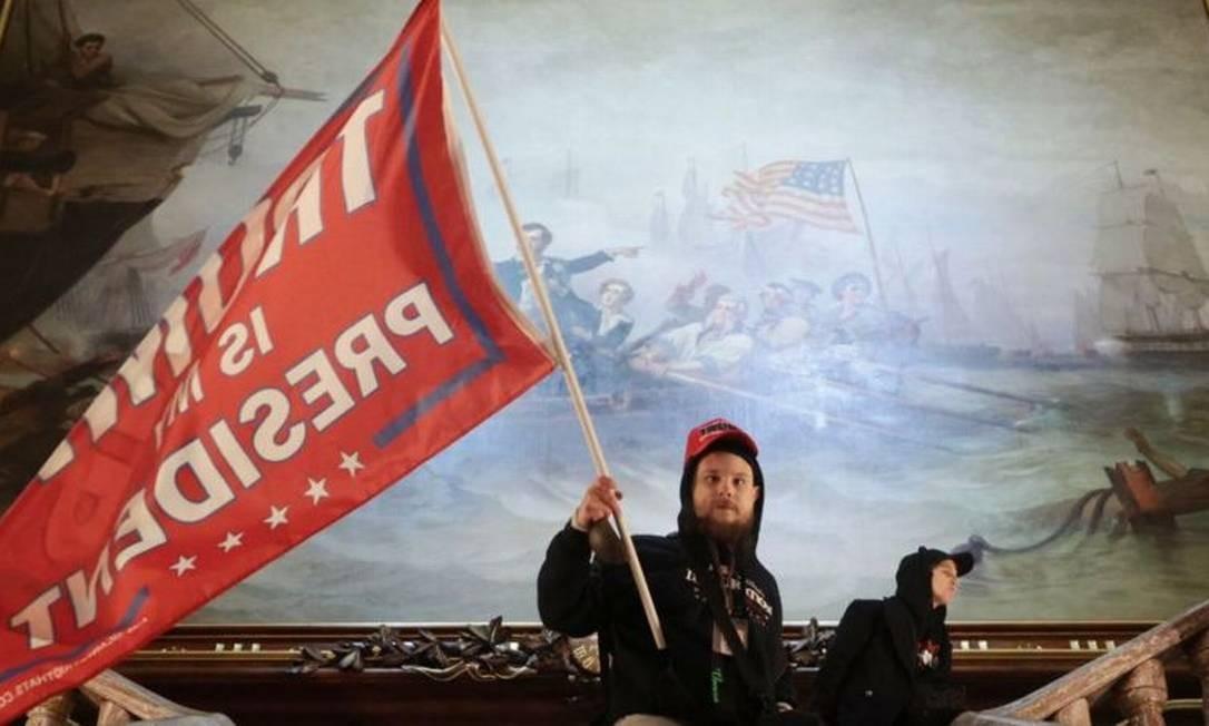 Invasor do Capitólio agita uma bandeira com os dizeres