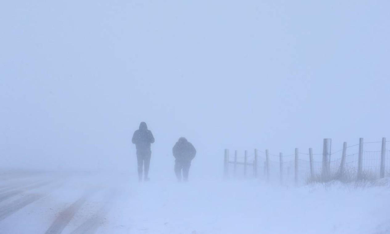 Duas pessoas caminham sobre a neve durante uma nevasca em Saddleworth, norte da Inglaterra Foto: LINDSEY PARNABY / AFP - 8/02/2021