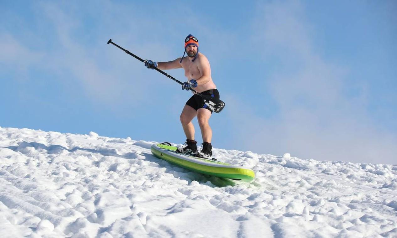 Homem desliza colina abaixo usando um stand-up paddleboard em um parque durante um dia nevado de inverno em Magdeburg, leste da Alemanha Foto: RONNY HARTMANN / AFP - 12/02/2021