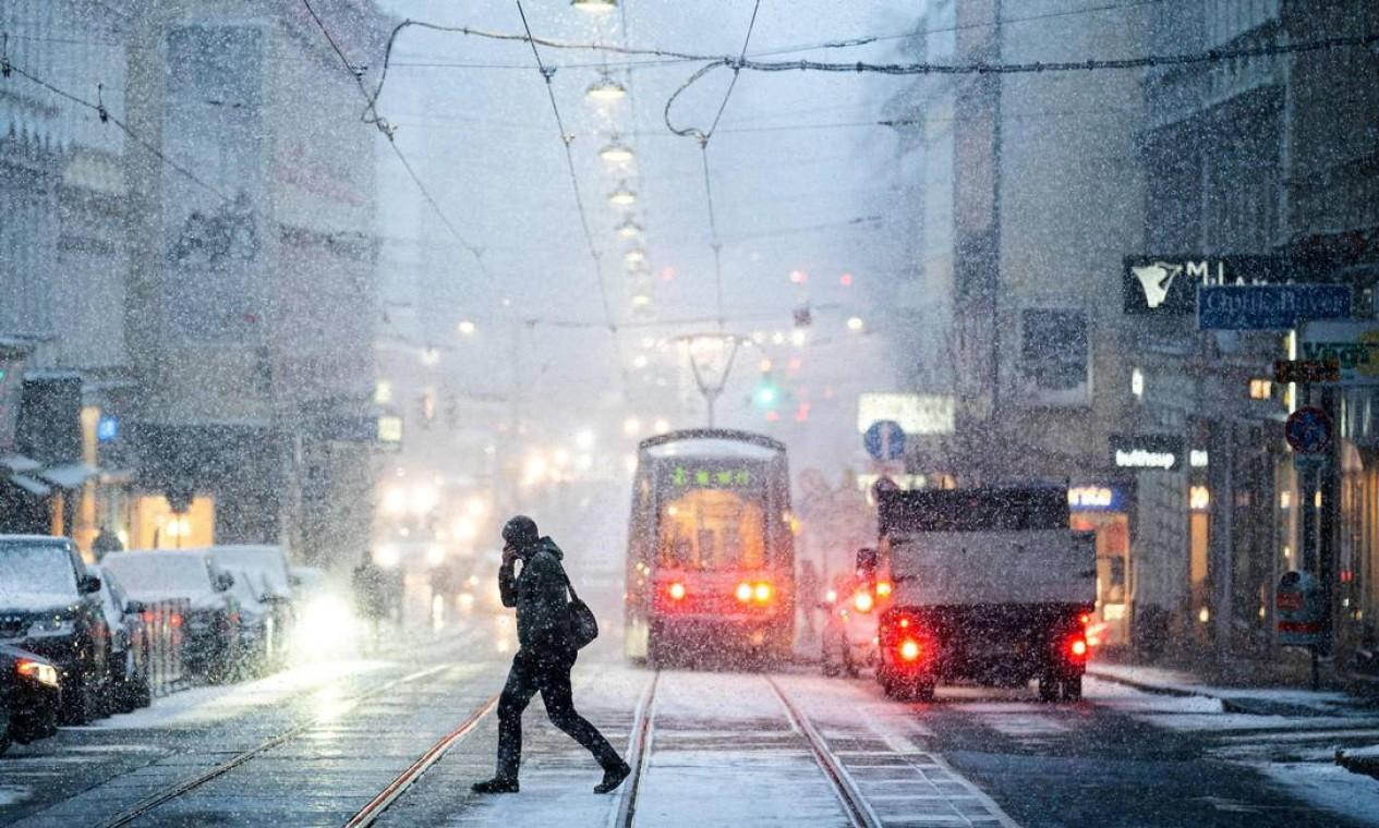 Homem atravessa uma rua durante uma nevasca em Viena, na Áustria Foto: GEORG HOCHMUTH / AFP - 11/02/2021