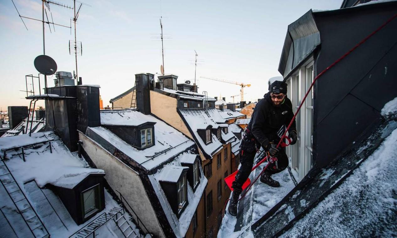 O removedor de neve de telhado Andrei Plian trabalha no topo de um dos edifícios da cidade velha de Stockholms, em Estocolmo Foto: JONATHAN NACKSTRAND / AFP - 11/02/2021