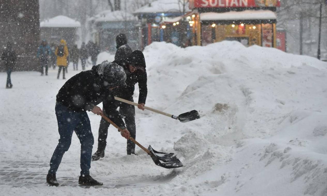 Vendedores limpam a neve perto de suas barracas no centro da capital ucraniana, Kiev Foto: SERGEI SUPINSKY / AFP - 11/02/2021