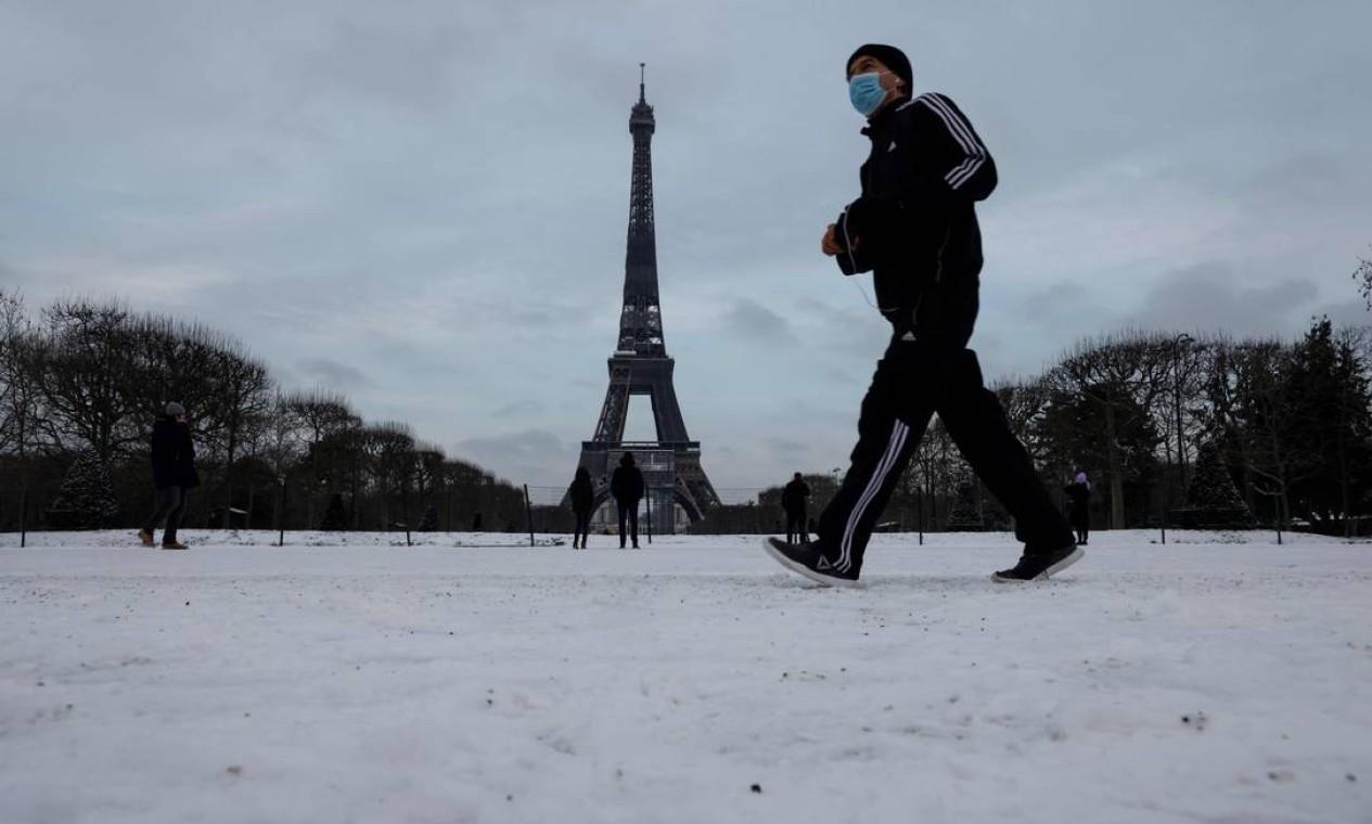 Homem passa pela Torre Eiffel após uma leve nevasca durante a noite, em Paris Foto: LUDOVIC MARIN / AFP 10/02/2021
