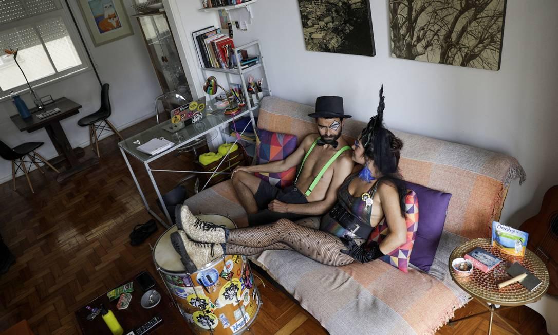 """Em casa: Giulia Tucci e seu marido, Marcelo Azevedo, usam fantasias que usariam durante os blocos de carnaval que desfilariam nessa época do ano. """"Carnaval para mim significa resistência e alegria, e as pessoas que ocupavam as ruas durante as festas carnavalescas também tinham sido um movimento de resistência política, mas este ano é preciso não ter essas festas, e a resistência real é evitar as ruas e estar em casa"""", disse a foliona Foto: RICARDO MORAES / REUTERS"""