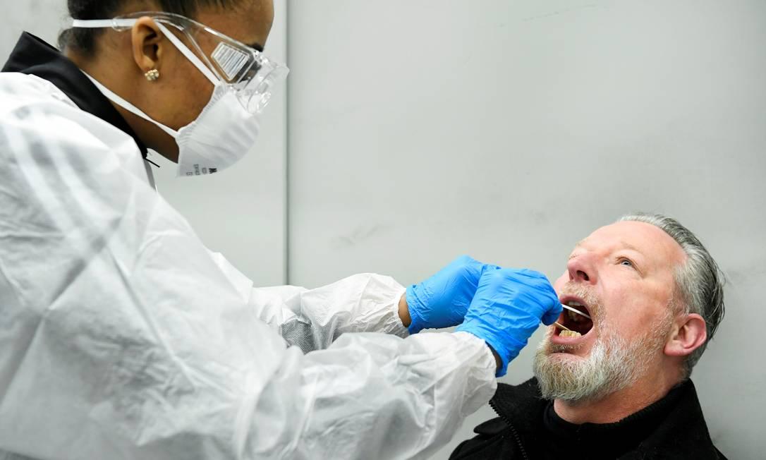 Membro da equipe médica coleta uma amostra de teste de coronavírus de um homem Foto: PIROSCHKA VAN DE WOUW / REUTERS