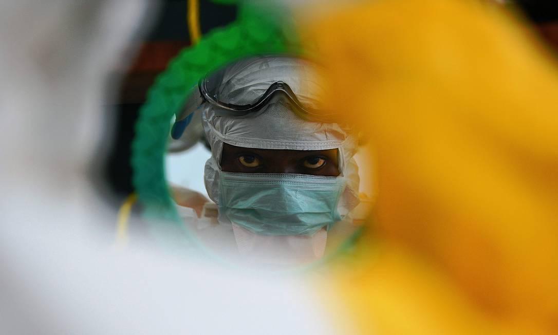 Foto de arquivo tirada em agosto de 2014 mostra um funcionário médico da organização Médicos Sem Fronteiras verificando suas roupas de proteção em um espelho em uma instalação em Kailahun, epicentro do pior surto de ebola Foto: CARL DE SOUZA / AFP
