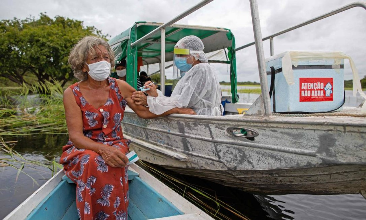 Olga D'arc Pimentel, 72 anos, é vacinada contra Covid-19, na comunidade Nossa Senhora Livramento, às margens do Rio Negro, perto de Manaus, Amazonas Foto: MICHAEL DANTAS / AFP
