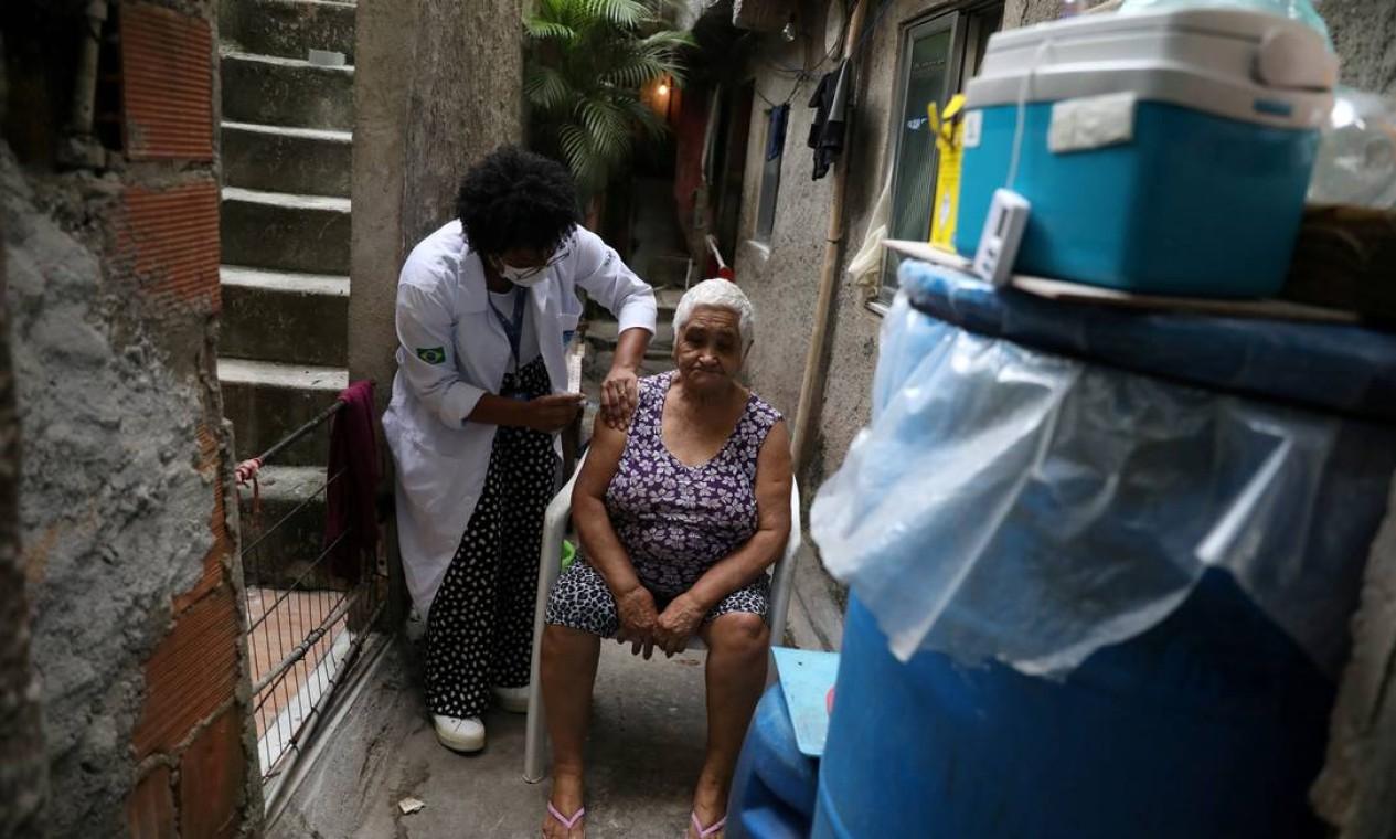 Maria do Socorro Correia, 78 anos, recebe vacina contra coronavírus em sua casa, na favela da Rocinha, no Rio de Janeiro Foto: PILAR OLIVARES / REUTERS
