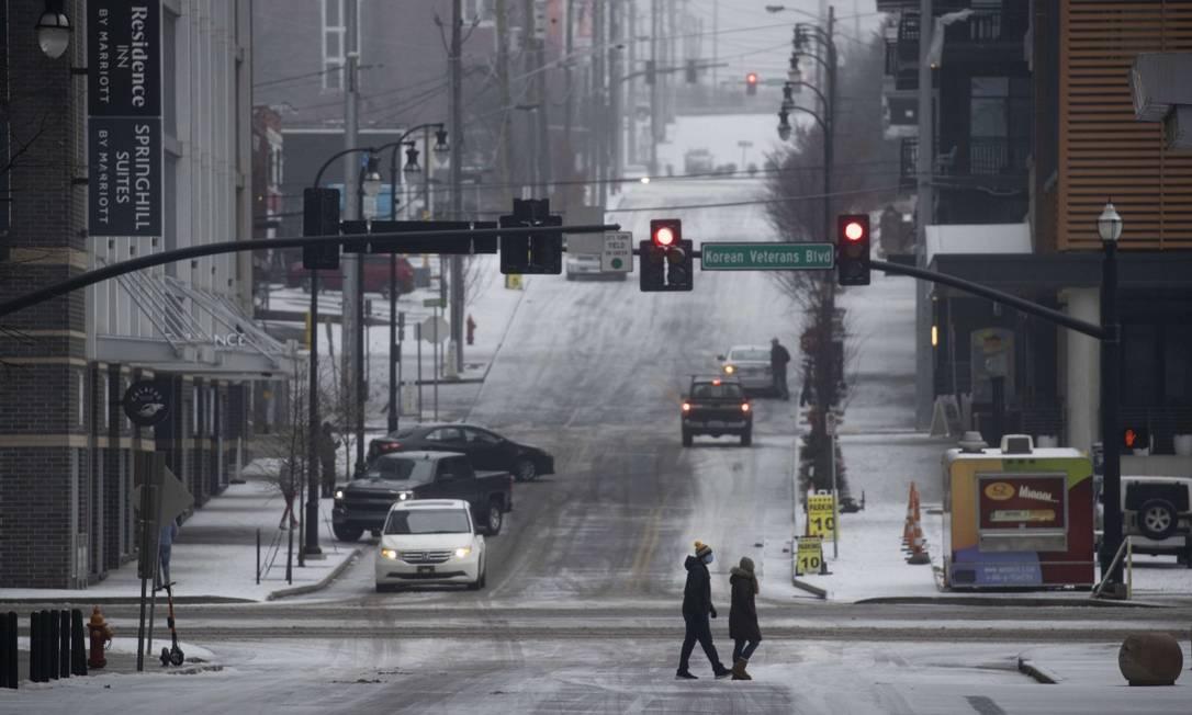 Pessoas atravessam calçadas cobertas de gelo no centro da cidade depois que uma mistura noturna de granizo e temperaturas congelantes cobriram a cidade de gelo em Nashville, Tennessee. As principais tempestades de inverno atingiram 26 estados com uma mistura de temperaturas congelantes e precipitação Foto: Brett Carlsen / AFP