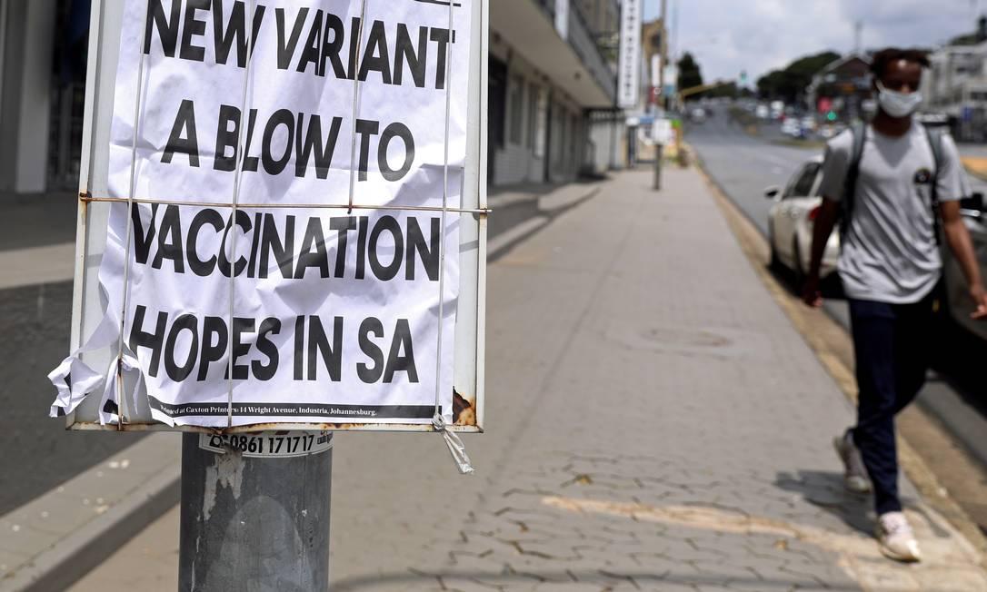 """Homem caminha diante de jornal anunciando a variante sul-africana do coronavírus como um """"revés"""" para a vacinação contra a Covid-19 na África do Sul em rua da capital do país, Johannesburgo, no último dia 8 Foto: SUMAYA HISHAM / REUTERS"""