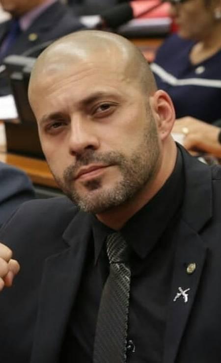 Com broche de armas na lapela do paletó, Daniel posa na Câmara dos Deputados Foto: Reprodução / Agência O Globo