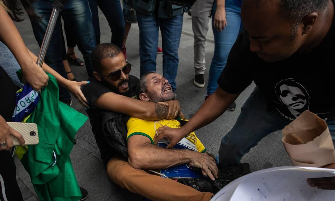 Bolsonarista estrangula manifestante enquanto comparça tenta pegar a placa com em homenagem à Marielle Franco Foto: Brenno Carvalho / Agência O Globo