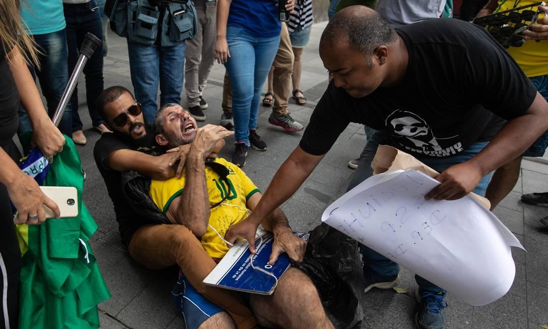 Rosa é agredido por apoiadores do deputado Daniel Silveira na porta da PF, na quarta-feira. Ativista teve placa em homenagem à Marielle Franco arrancada dele Foto: Brenno Carvalho / Agência O Globo