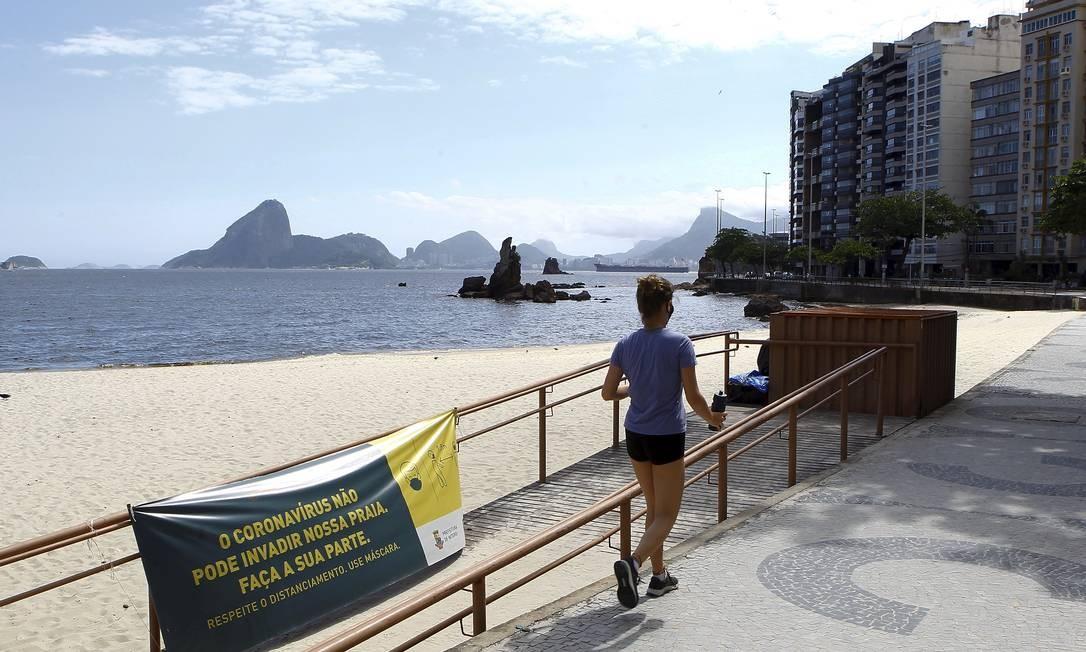 Sem aglomeração: mulher caminha sozinha no calçadão de Icaraí Foto: Guilherme Pinto / Agência O Globo