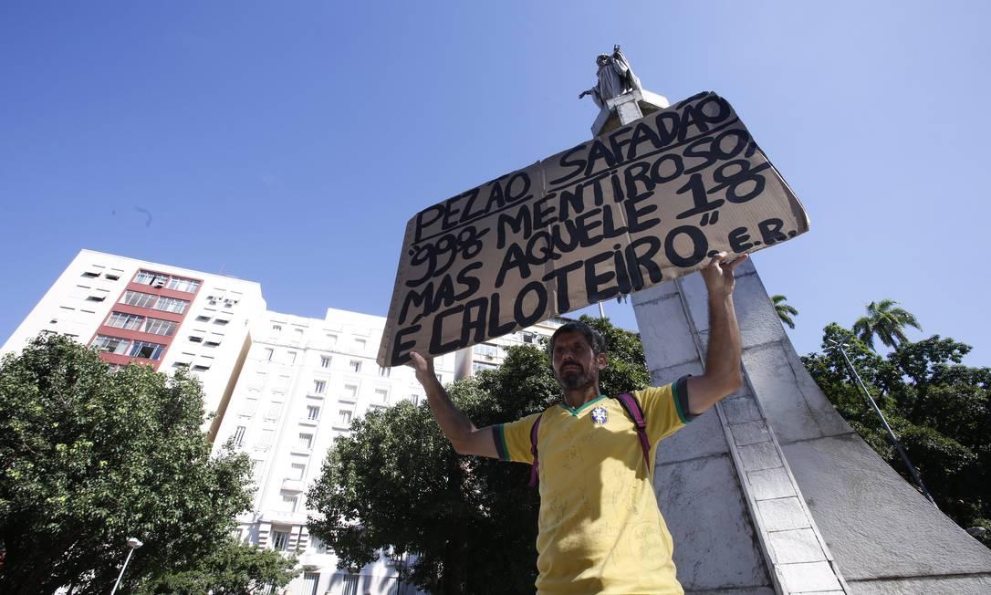 Rosa ergue um dos seus cartazes durante protesto de servidores estaduais no Largo do Machado Foto: Thiago Freitas / Agência O Globo