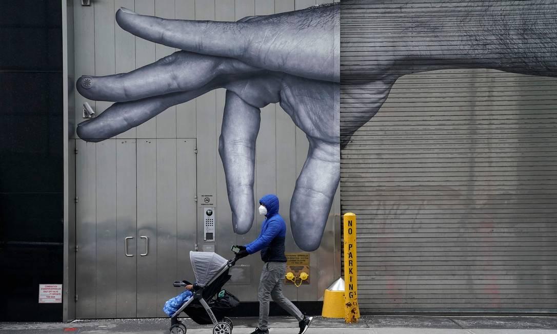 Americano de máscara passeia com bebê pelas ruas de Nova York Foto: TIMOTHY A. CLARY / AFP