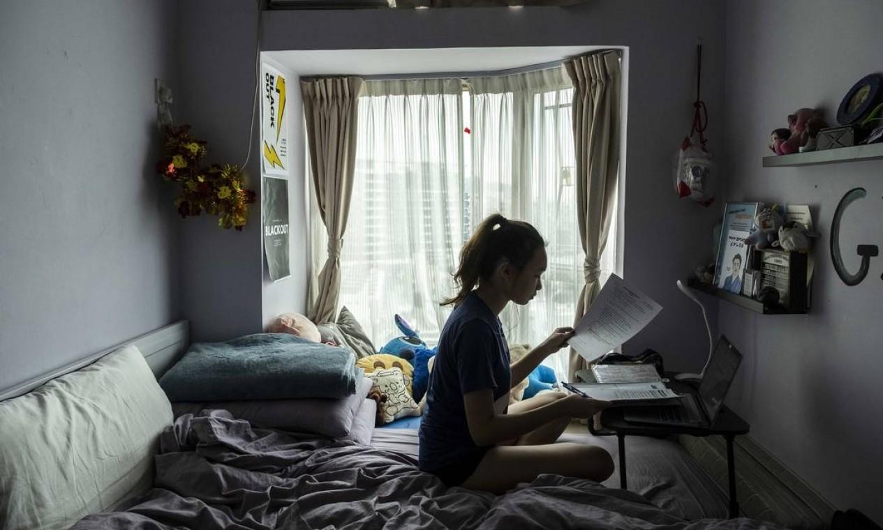 Chloe Lau, estudante do ensino médio, faz seus trabalhos escolares em casa em Hong Kong, em março de 2020. Coronavírus forçou diversos países, bem como províncias, cidades e vilas, a fechar escolas em um esforço para conter a propagação do surto, deixando centenas de milhões de alunos em todo o mundo sem ir à escola Foto: LAM YIK FEI / The New York Times