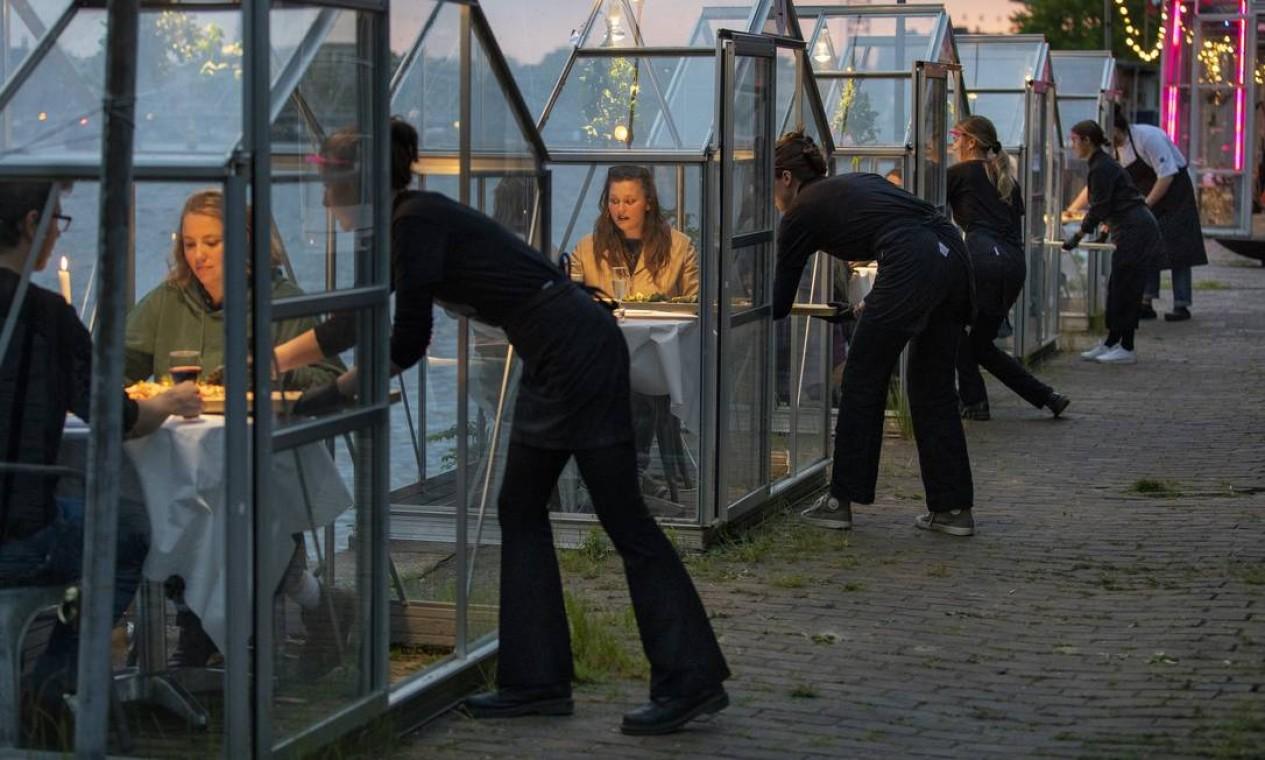 Hóspedes são servidos em cabines de vidro no restaurante Mediamatic ETEN, em Amsterdã, em maio de 2020. Ensaio da nova configuração, que torna o distanciamento social, conforme exigido, mais viável quando os restaurantes conquistaram permissão para reabrir Foto: ILVY NJIOKIKTJIEN / The New York Times