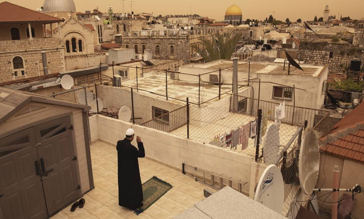 Homem ora em um telhado durante as orações da tarde do Ramadã em Jerusalém, em abril de 2020. A pandemia do coronavírus transformou como os muçulmanos em Israel e nos territórios palestinos estão experimentando a data sagrada Foto: DAN BALILTY / The New York Times