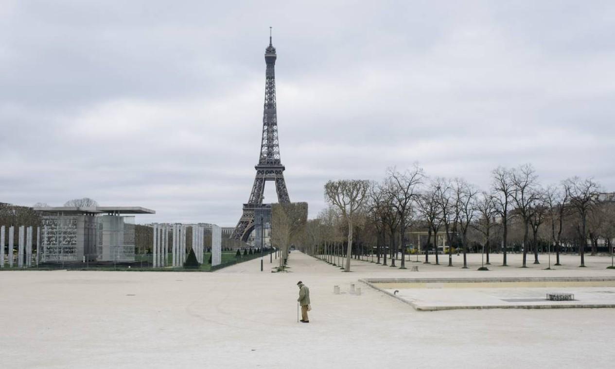 Homem caminha no Champ de Mars, perto da Torre Eiffel, durante as restrições ao coronavírus em Paris, em março de 2020. Depois de um início desastrado, a União Europeia e suas instituições, incluindo o Banco Central Europeu, começaram a lidar melhor com o novo desafio da Europa como epicentro do vírus Foto: DMITRY KOSTYUKOV / The New York Times