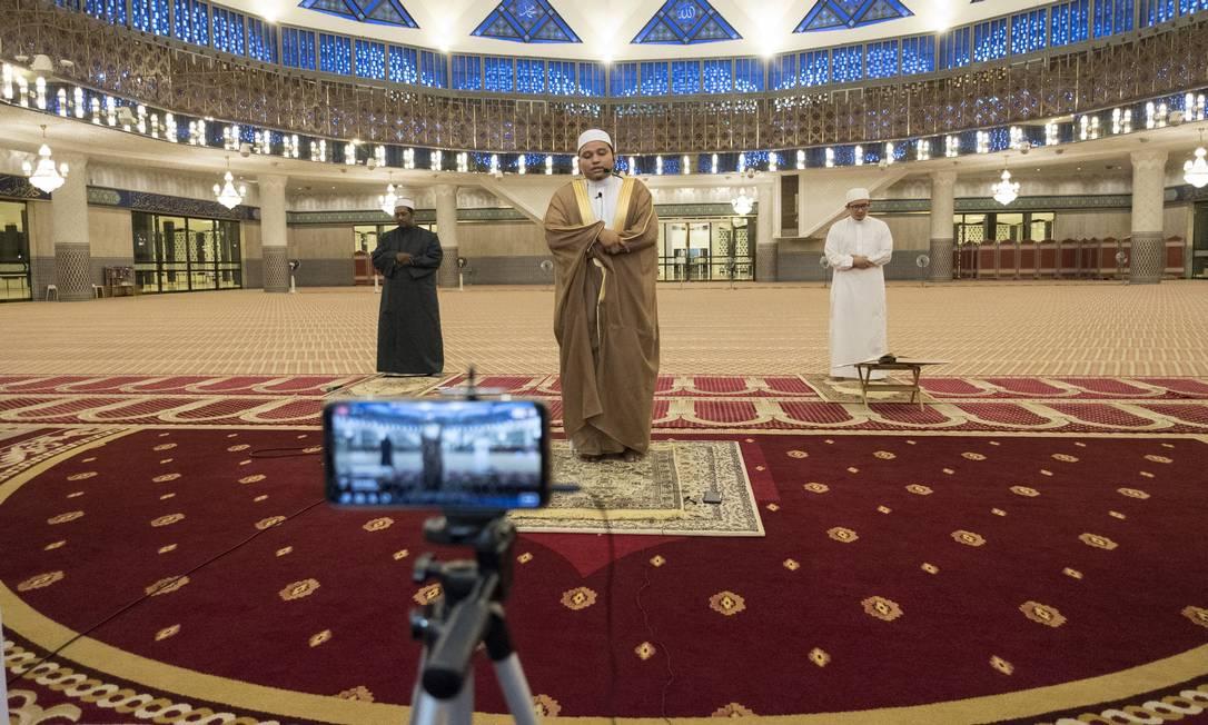Um imã e seus assistentes realizam a oração de Tarawih na Mesquita Nacional em Kuala Lumpur, Malásia, em abril de 2020. Locais mais sagrados do Islã estavam em grande parte desertos no primeiro dia do mês sagrado do Ramadã Foto: ALEXANDRA RADU / The New York Times