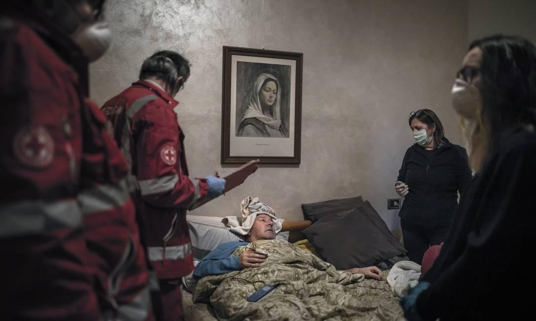 Claudio Travelli, 61, inifectado pelo coronavírus, é examinado em sua casa em Cenate Sotto, Itália, em 15 de março de 2020. No dia seguinte, sua família chamou novamente uma ambulância porque seu quadro havia piorado Foto: FABIO BUCCIARELLI / The New York Times