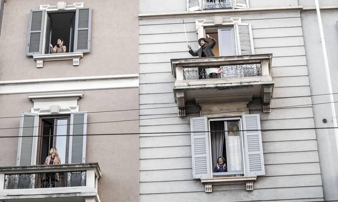 Vizinhos interagem das sacadas de seus apartamentos em Milão, Itália, em março de 2020. Novas formas de socializar em tempos de pandemia Foto: ALESSANDRO GRASSANI / The New York Times