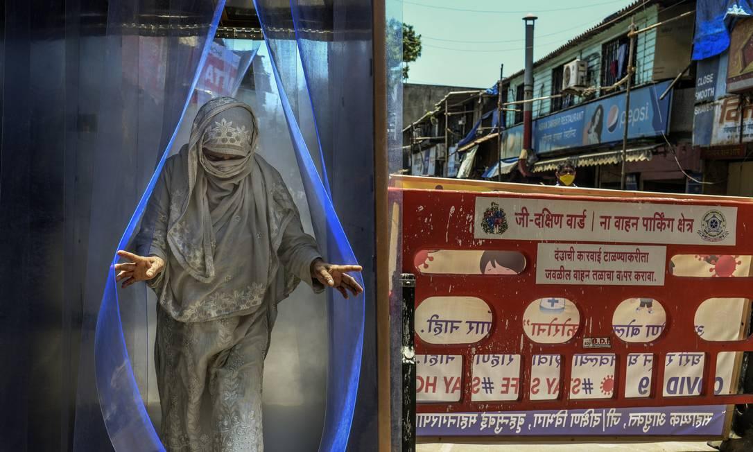 Mulher passa por um túnel de desinfecção em Mumbai, em abril de 2020. Cidade de 20 milhões de habitantes é agora responsável por 20% das infecções por coronavírus na Índia e quase 25% das mortes Foto: ATUL LOKE / The New York Times