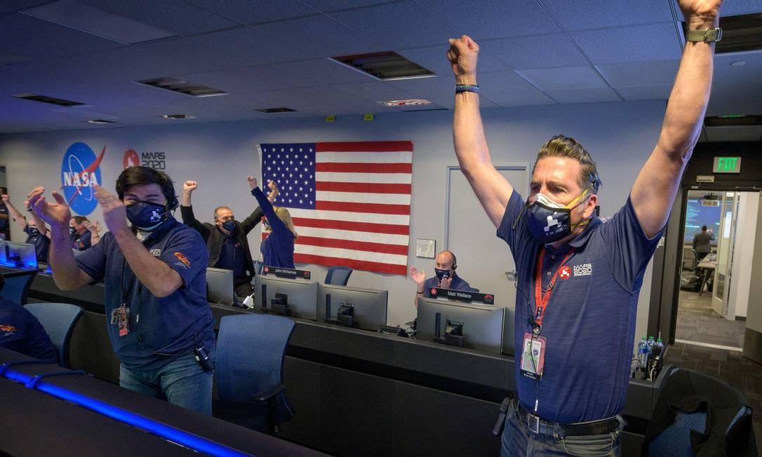 Equipe da Nasa comemoram, após receber a confirmação de que a espaçonave Perseverance pousou com sucesso em Marte Foto: BILL INGALLS / AFP