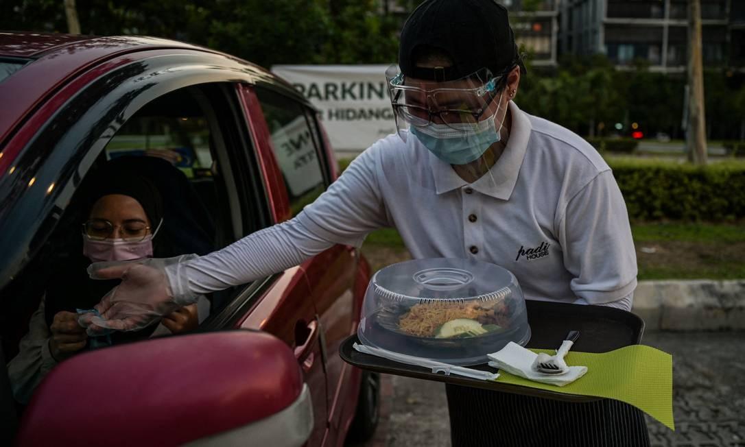Para amenizar a fadiga do isolamentgo social, na capital da Malásia, Kuala Lumpur, restaurantes estão servindo jantares a clientes a bordos do próprio carro Foto: MOHD RASFAN / AFP