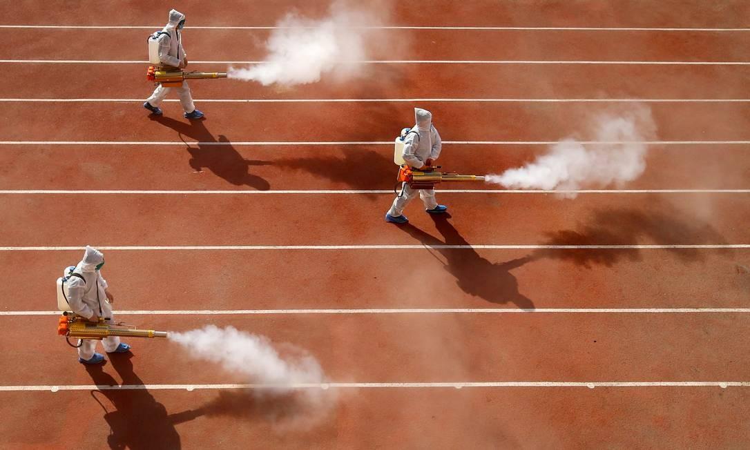Trabalhadores borrifam desinfetante na pista de atletismo de uma escola primária em Huaibei, na província de Anhui, leste da China Foto: STR / AFP