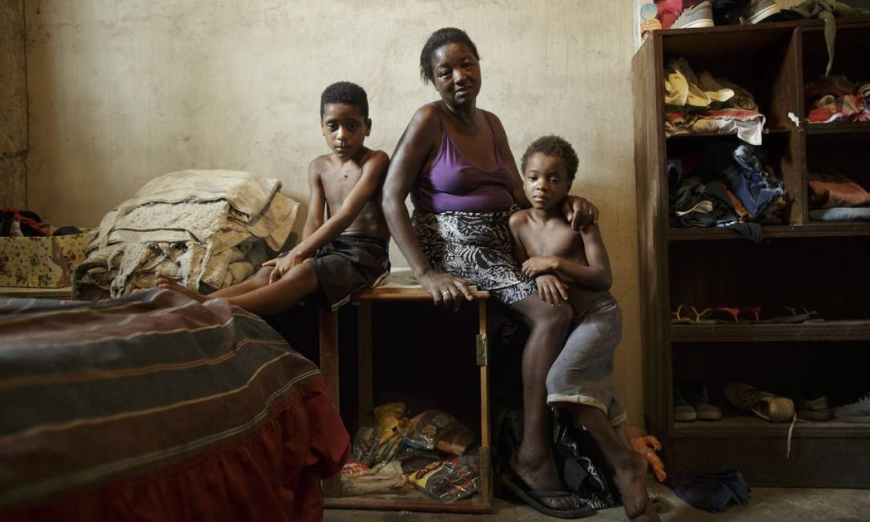 No caixote onde Simone está sentada, estão guardados os poucos mantimentos que se tem para a família, um pouco de farinha e feijão Foto: Márcia Foletto / Agência O Globo