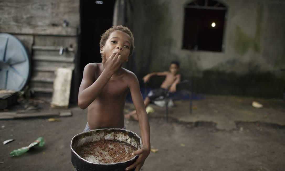 A pequena Aline come as migalhas de um bolo Foto: Márcia Foletto / Agência O Globo