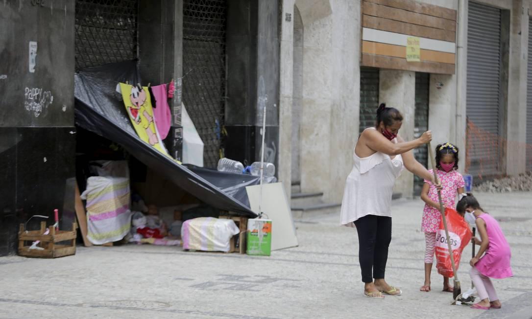 Ana Paula e as filhas varrem a calçada em que vivem, no Centro do Rio Foto: Domingos Peixoto / Agência O Globo