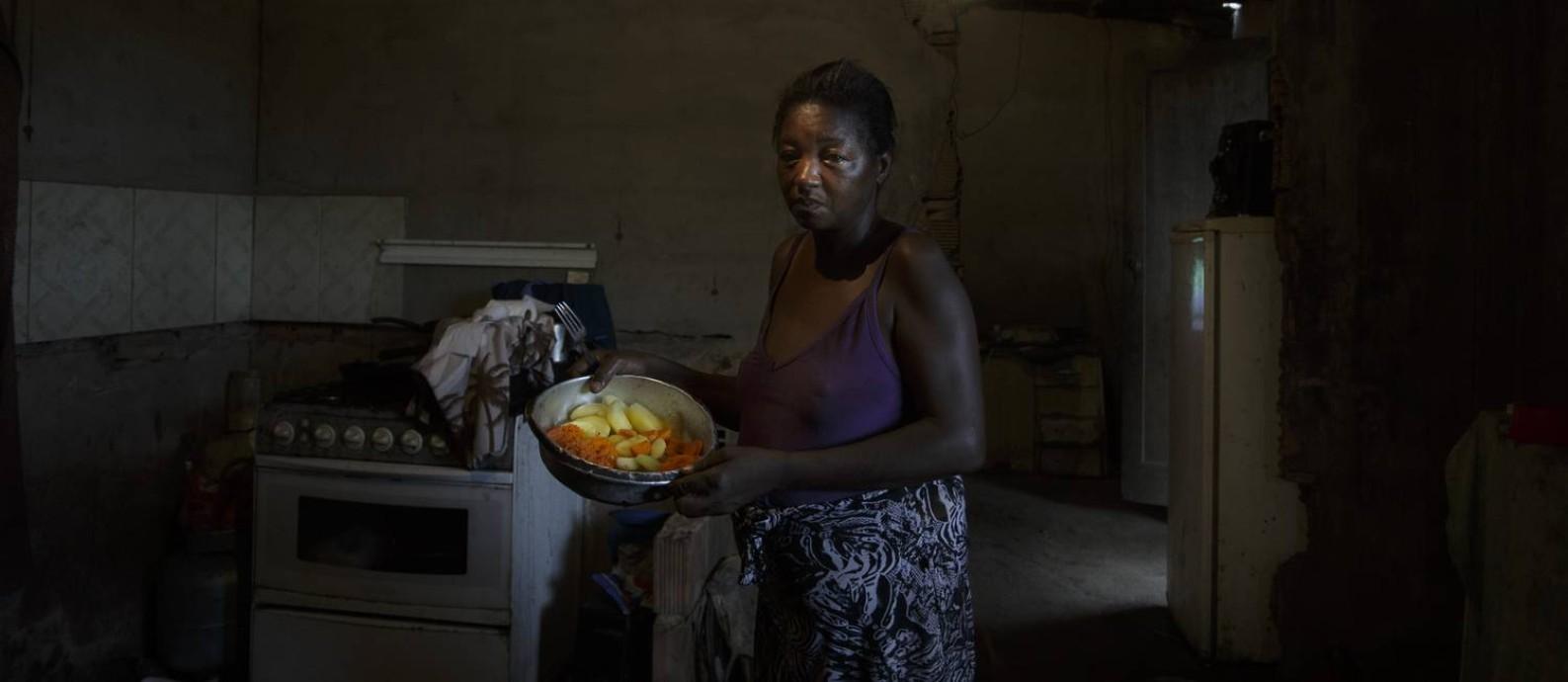 Simone Souza Bernardes, 49 anos, mostra os legumes que ganhou de um vizinho: jantar será a única refeição da família no dia Foto: Márcia Foletto / Agência O Globo