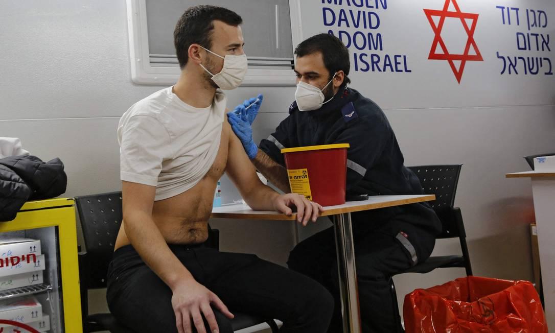 Profissional de saúde administra vacina contra Covid-19 em Tel Aviv Foto: GIL COHEN-MAGEN / AFP