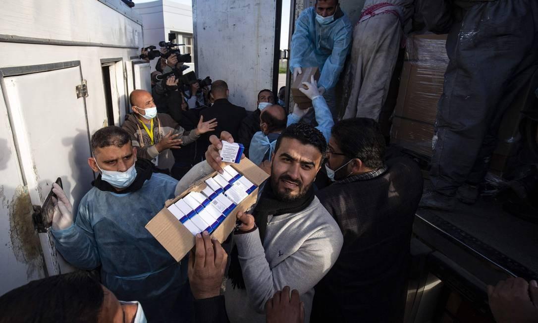 Trabalhadores descarregam caminhão comdoses da vacina russa Sputnik V, enviada dos Emirados Árabes Unidos, para a Faixa de Gaza através da travessia de Rafah com o Egito. Cerca de 20.000 doses da vacina contra o coronavírus dos Emirados Árabes Unidos chegou a Gaza hoje, uma entrega supostamente orquestrada por um rival do presidente palestino Mahmud Abbas três meses antes das eleições palestinas marcadas Foto: SAID KHATIB / AFP
