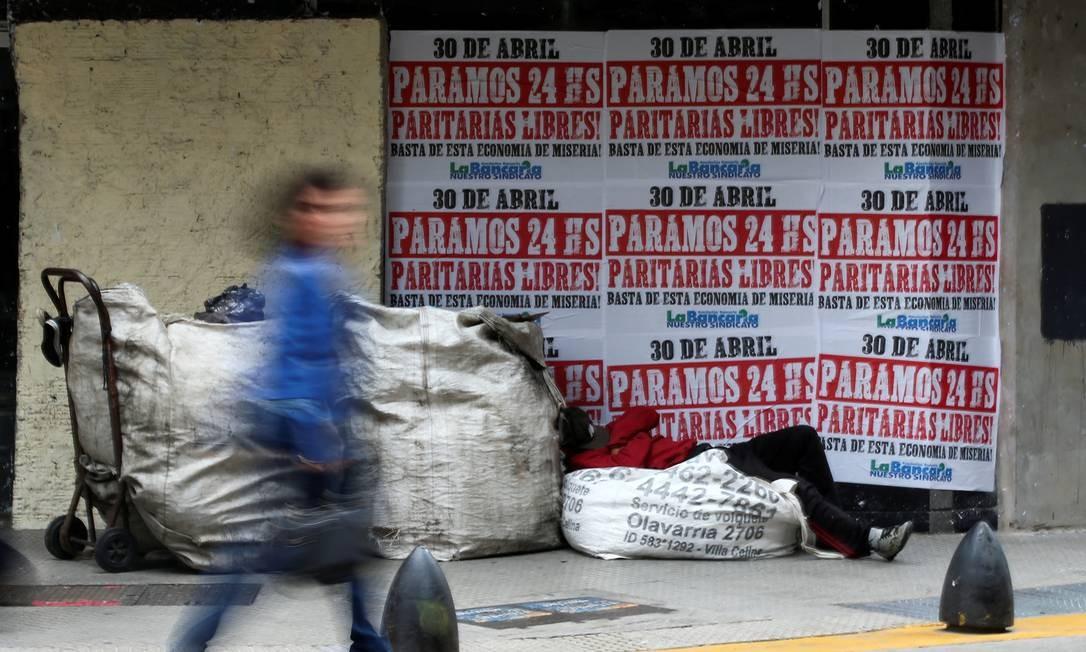 Morador de rua dorme do lado de fora de uma casa de câmbio com cartazes anunciando uma greve geral, em abril de 2019; país experimenta, desde 2018, um coquetel de disparada do dólar, dos juros, da inflação e do desemprego Foto: Agustin Marcarian / Reuters