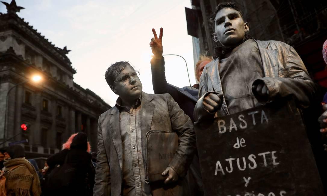 """Manifestantes pintados de cinza seguram uma placa que diz """"Chega de demissões nem ajustes"""" durante um protesto em Buenos Aires, em 2018 Foto: Marcos Brindicci / Reuters"""