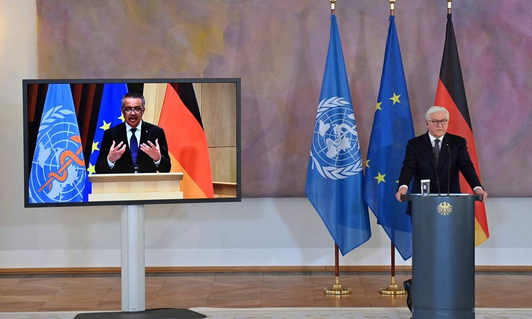 O diretor-geral da OMS, Tedros Adhanom Ghebreyesus (à esquerda, na TV) participa de videoconferência com o presidente da Alemanha, Frank-Walter Steinmeier, nesta segunda-feira (22) Foto: JOHN MACDOUGALL / AFP