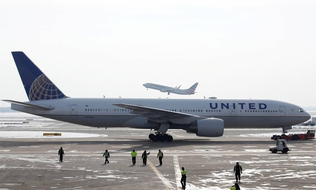 Boeing 777-200ER da United Airlines é rebocado enquanto um Boeing 737 da American Airlines decola do Aeroporto Internacional O'Hare, em Chicago, Illinois, EUA, em novembro de 2018. Nova crise atinge a gigante da aviação dos Estados Unidos, que foi forçada a encalhar outra frota de aviões após uma série de quedas mortais Foto: Kamil Krzaczynski / REUTERS - 30/11/2018