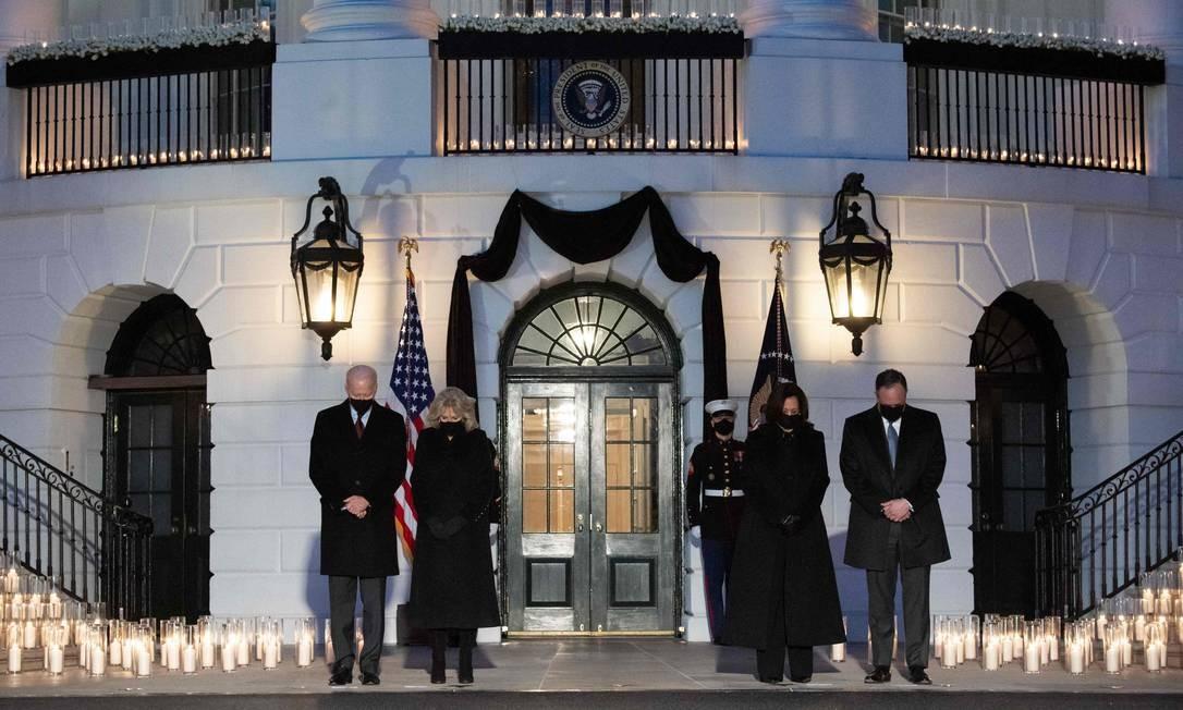 O presidente dos EUA Joe Biden, a primeira-dama Jill Biden, a vice-presidente dos EUA Kamala Harris e seu marido, Doug Emhoff, prestam momento de silêncio durante uma cerimônia à luz de velas em homenagem às 500-mil vítimas do coronavírus nos Estados Unidos. A cerimônia aconteceu no gramado sul da Casa Branca, em Washington Foto: SAUL LOEB / AFP
