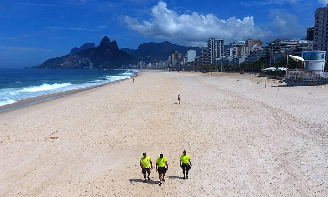 O inimaginável: policiais fiscalizam a praia de Ipanema, em pleno domingo de sol, em março de 2020. No início da pandemia, medidas de restrição incluíram o fechamento, inclusive, do principal lazer do carioca Foto: Fábio Motta / Agência O Globo - 29/03/2020
