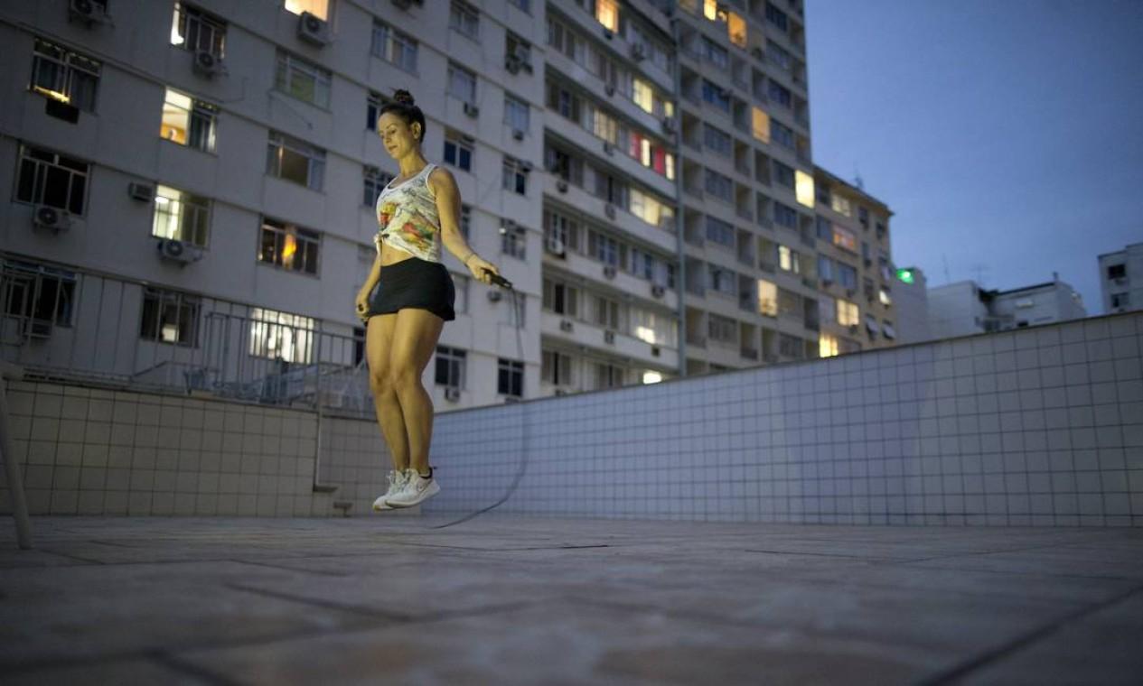 Home Gym: na quarentena, alternativa é fazer exercícios físicos em casa. Na foto, a advogada Juliane Ribeiro, que passou a fazer aulas online na varanda e pular corda na piscina do prédio onde mora, em Copacabana Foto: Márcia Foletto / Agência O Globo - 14/04/2020