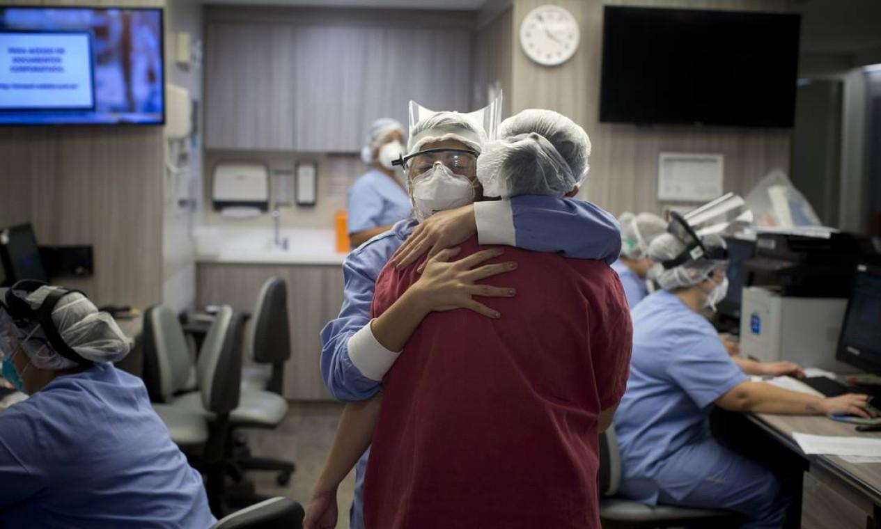 Fuga do protocolo, mas à procura de conforto. Membros de equipe médico se abraçam em meio ao estresse na linha de frente contra a Covid-19, na UTI do Hospital Copa Star, em Copacabana Foto: Márcia Foletto / Agência O Globo - 16/04/2020