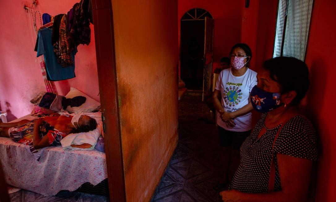 O corpo de Francisca Ribeiro Bentes, 75 anos, é visto sobre a cama enquanto a filha, Elaine Bentes Carneiro, de 55 anos, aguarda a remoção, em Manaus Foto: Yan Boechat / Agência O Globo - 30/04/2020