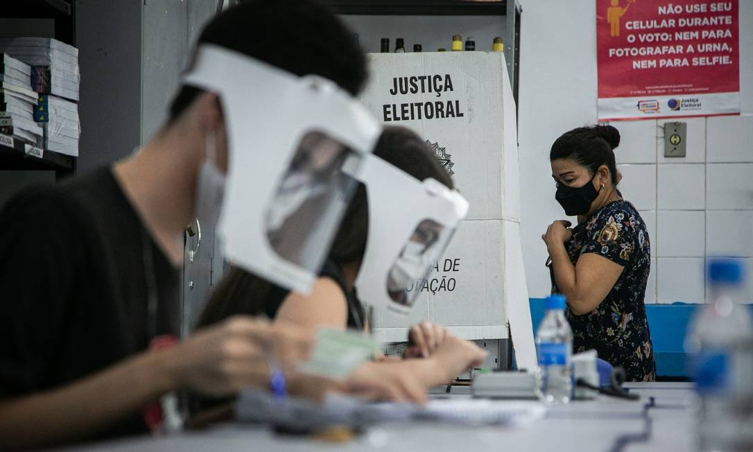Eleições municipais em tempos de pandemia. Eleitora se dirige para cabine de votação no Ciep Ayrton Senna da Silva, na Rocinha: máscara e álcool em gel foram tão necessários quanto o título eleitoral Foto: Hermes de Paula / Agência O Globo - 15/11/2020