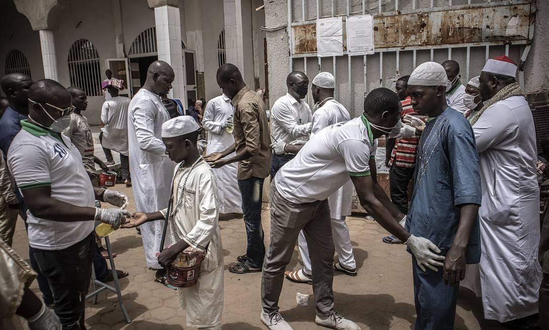 Fiéis são revistados e sanitizados antes de participarem das orações na Grande Mesquita, na capital de Burkina Fasos, Ouagadougou, para tentar evitar possível contágio da Covid-19 Foto: FINBARR O'REILLY / Agência O Globo - 13/03/2020
