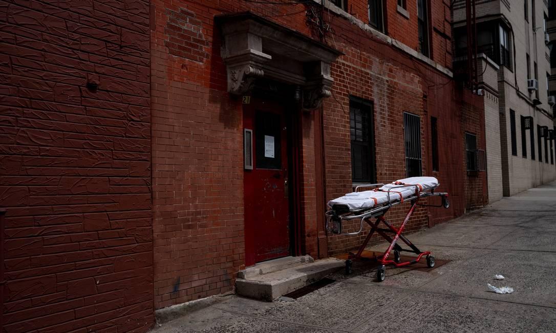 Uma maca é vista estacionada em frente a um prédio de apartamentos em Nova York enquanto uma equipe médica trabalhava em um paciente dentro do prédio. O paciente foi reanimado na ambulância, mas morreu antes de chegar ao hospita Foto: ERIN SCHAFF / Agência O Globo - 20/04/2020